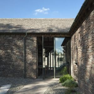 Barn Conversion. Perpendicular corner of L-shaped barn. The original stone walls have stood for an age and there is a two story window where the two walls join. The slate roof catches the sun in the car blue sky. Communion Architects, Hereford.