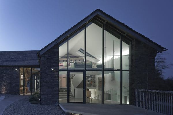 A stone 16th century, now a modern day barn conversion, photo taken at dusk showing a two storey glazed wall, through the glass can be seen a floating staircase with a curving steel banister and a a seating area on the first floor mezzaine.
