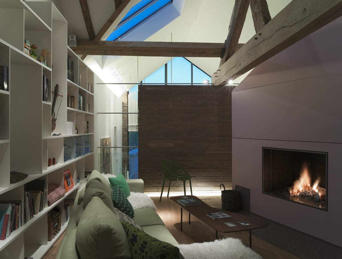 Interior of barn conversion. Left hand sided is an open bookcase, in front is a green sofa, which sits in front of am open fire, set into a lilac wall on the right hand side of the frame.
