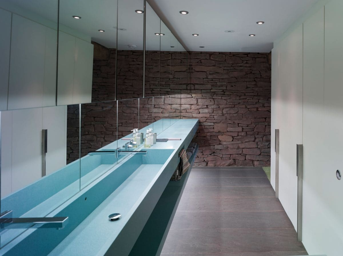 Looking along a bathroom in a barn conversion. The Left hand wall is covered in mirror from the ceiling down to the long blue steel sink with two silver taps. The end wall is original stone from the 15th barn. The right hand side was pale blue floor to ceiling doors for the cubicles. Barn conversion, communion architects Herefordshire