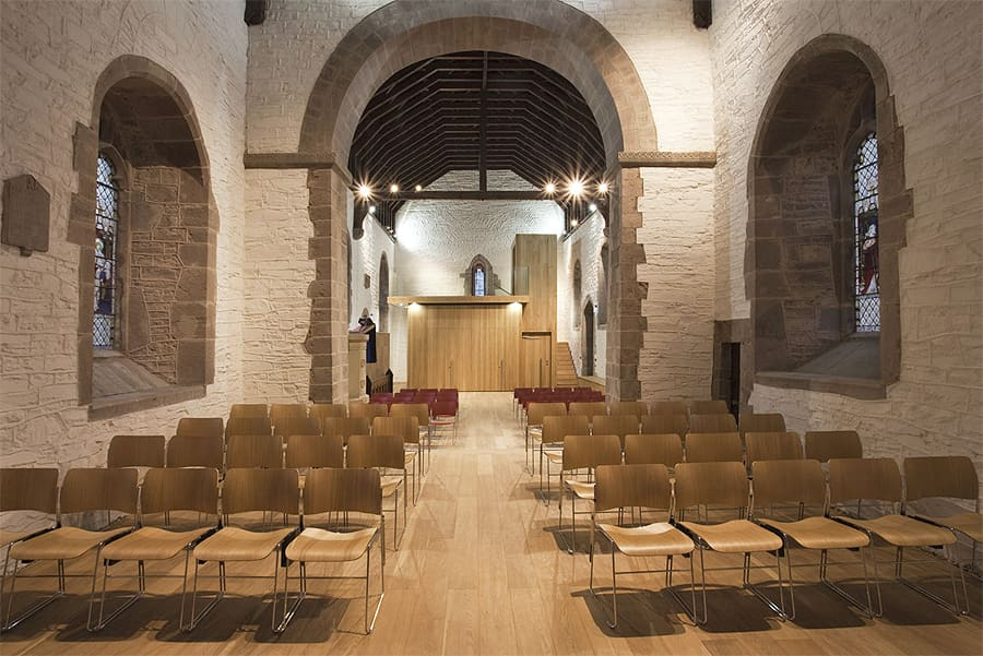 church re-ordering interior, looking down the central nave. Walls painted white with exposed stone framing the windows and central arch. A wooden flooring supports a rows of chairs, with space left for the central aisle. At the far end of the nave is a wood cube-like structure, this contains a kitchen area (unseen).