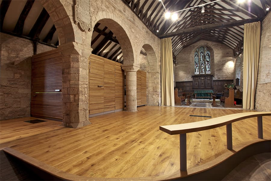 Interior of st Andrews, church re-ordering, a new timber floor has been added and in the back left is a timber cube behind pillars, this contains a kitchen and toilet facilities, unseen.