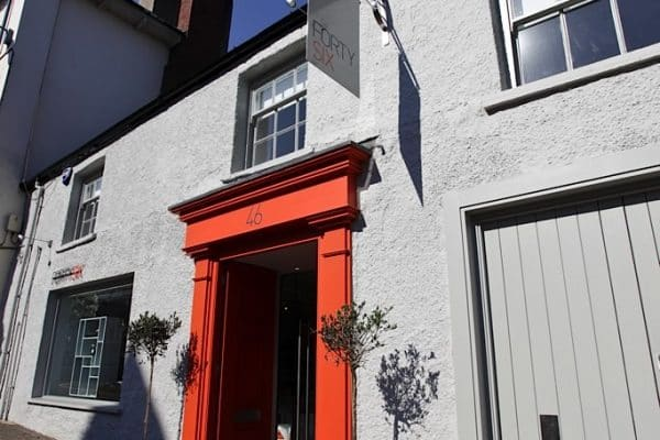 Creation of A New Retail Environment. Exterior of victorian terrace, painted white with red door frame.
