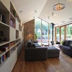 Interior of a home extension, left hand wall open bookcase, right hand wall and far back wall is glazed with timber frames, in the centre are two grey sofas on a oak floor.