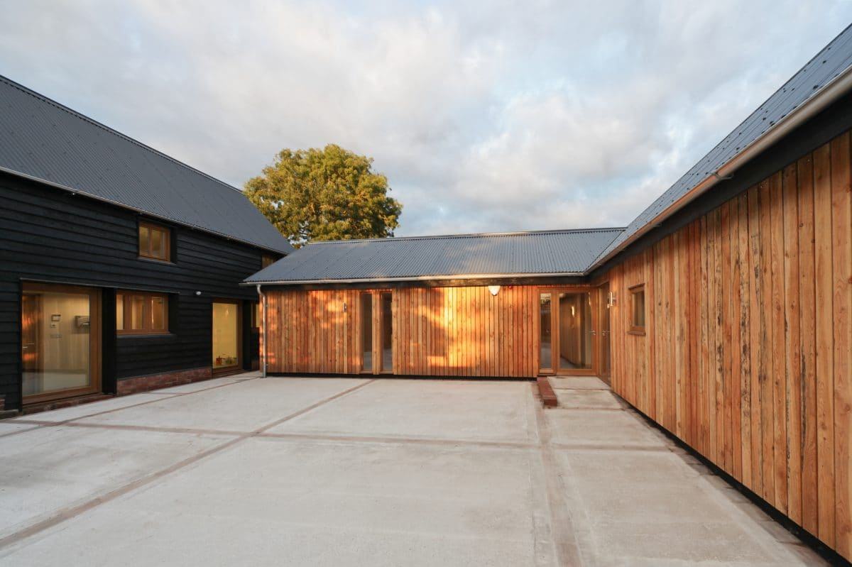 Perpendicular corner of an L-shaped barn conversion. The single storey exterior is rendered with vertical planks of timber, interrupted with full height glazing. The warm evening light creates a warm, orange image for this barn conversion and business, Communion Architects, Herefordshire.
