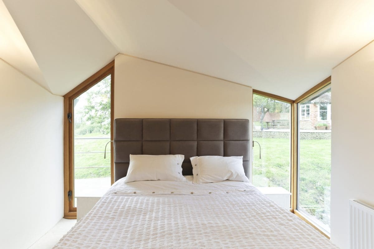 Image of light and airy bedroom with angled ceiling and zigzagging, timber-framed windows.