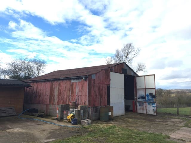 A tired looking industrial style agricultural barn. Breeze block base with corrugated steel walls with red peeling paint. The two storey door at the end swings open showing sprayed painted areas. This dilapidated barn can be transformed into a stunning barn conversion with some help. Communion Architects, Hereford.
