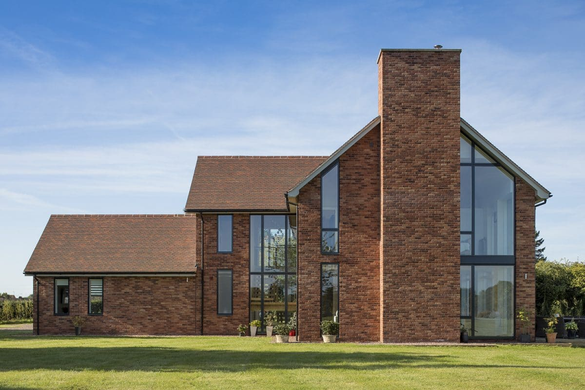Impressive large brick and glass home, bespoke new build house, featuring two storey glazed windows.