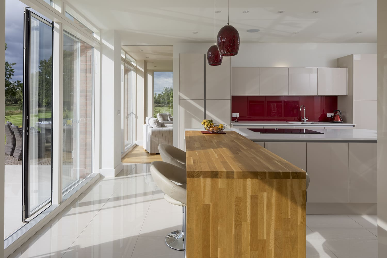 Sleek lines in modern kitchen with wood block breakfast bar, light filled from glazed wall on left hand side. The kitchen in the background is white with a red splash board.