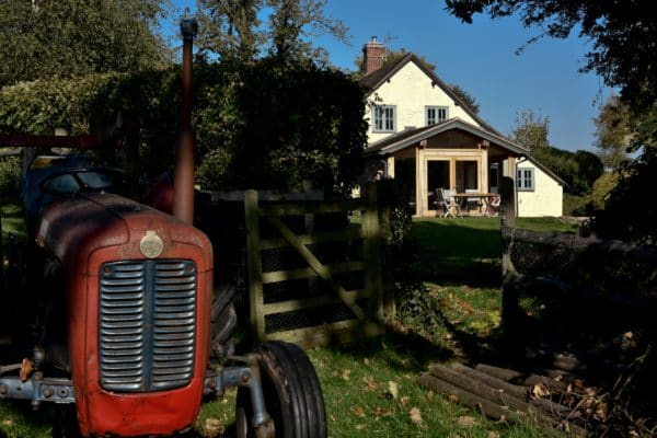 timber framed extension for a cider embassy, image taken from a distance featuring a red tractor in the foreground, communion architects Herefordshire