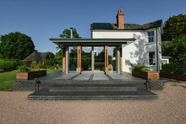 A glazed and aluminium extension with oak pillars, on a raised patio. Home extension by Communion Architects