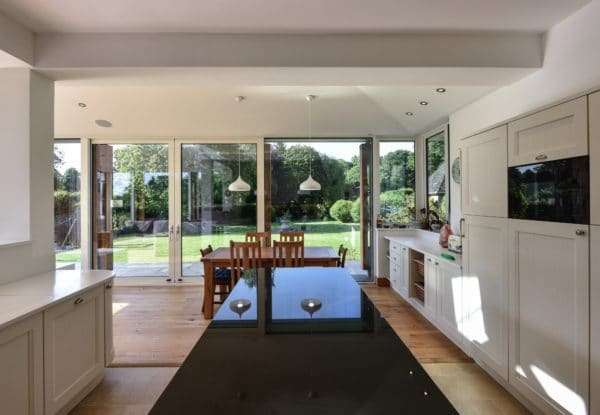 Interior of Home Extension. A black, marble kitchen island in a white kitchen, in the background the wooden dining table can be seen with a glazed wall behind it. Communion Architects Herefordshire.