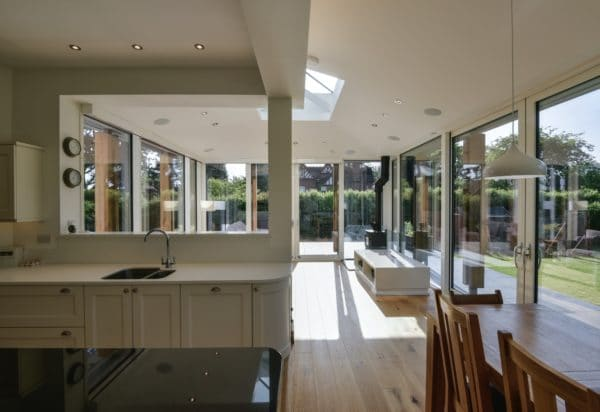 Home extension. An open plan kitchen to the left and dining area to the right. Behind these is a seating area, with three walls of glazing. This creates a light filled living area for the family. Communion Architects, Herefordshire.