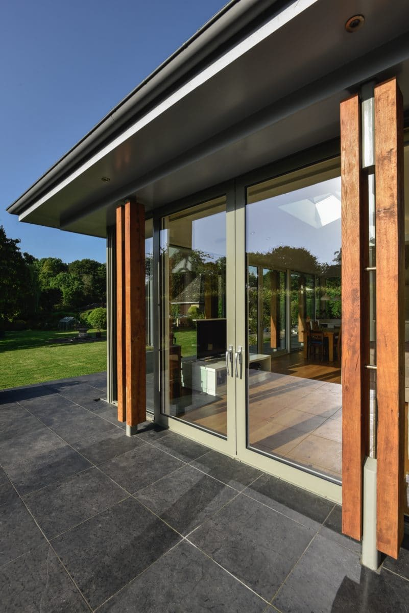 Exterior of home extension, close up of glazed sliding doors closed with timber columns either side. Communion Architects Herefordshire