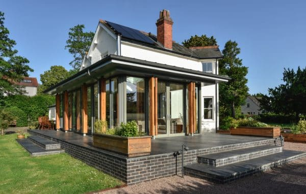Home extension with original 1930s house in the background. Communion Architects, Herefordshire.