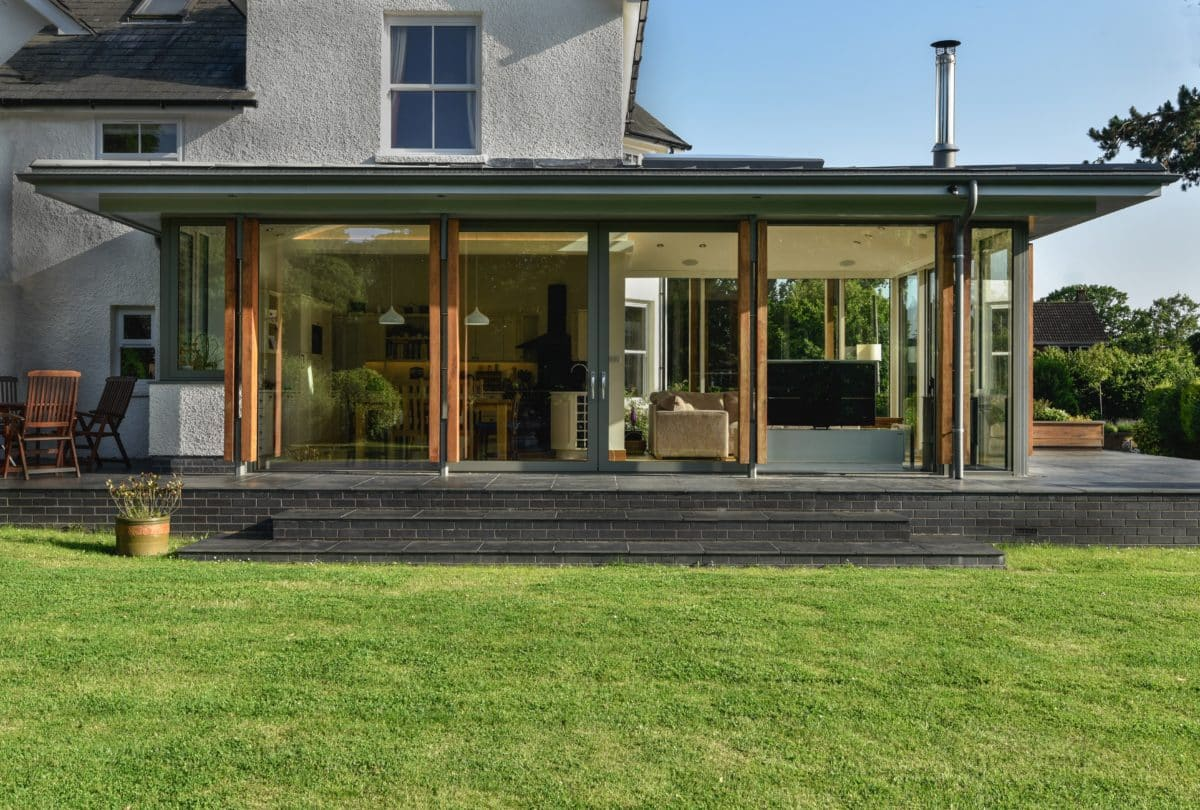 Tripartite image of home extension. Lower third is occupied by green grass, middle third features the low, glazed extension with a flat zinc roof, the upper third shows the original house rising in the background and the blue sky. Communion Architects, Herefordshire.