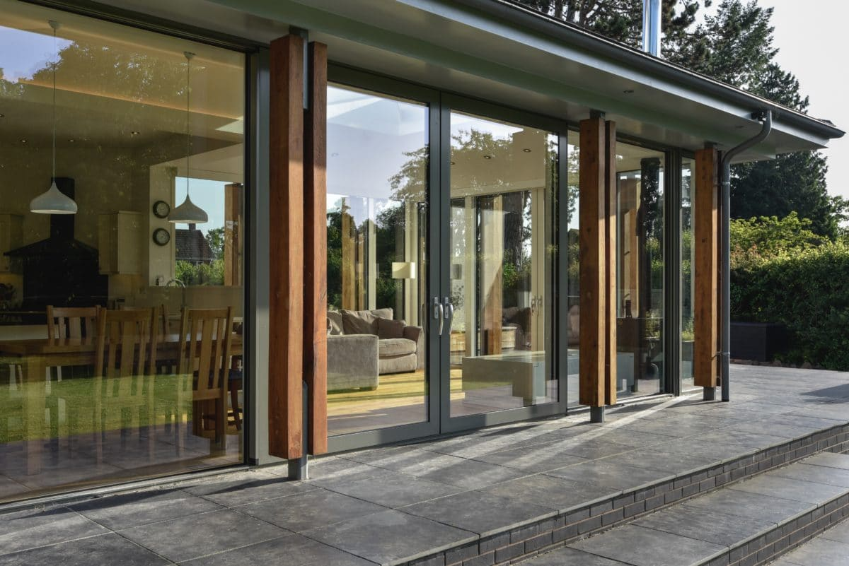 Close-up of sliding doors of the glazed extension. Floor to ceiling windows and doors, pictured, create a light-filled living area. Communion Architects, Herefordshire.