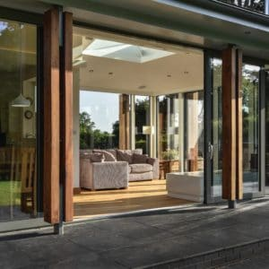 Sliding doors open to the home extension. The opening leads to the open plan living area, with additional sunlight let in through the roof opening. Communion Architects, Herefordshire.