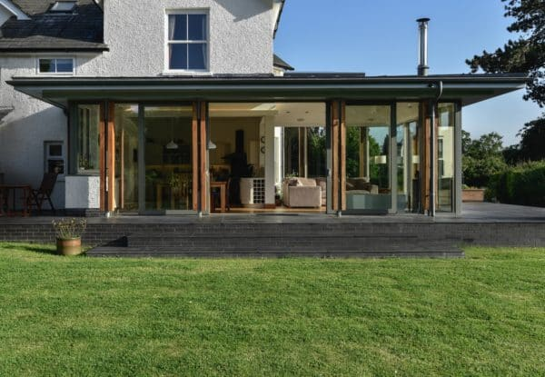 Tripartite image of grass, glazed extension and the original house and sky in the upper third. The doors to the glazed and aluminium extension are open, welcoming people in. Communion Architects, Herefordshire.