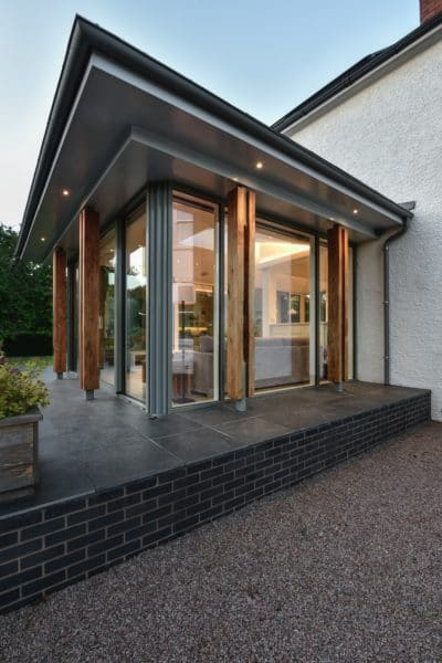 corner of home extension at dusk, the angle of the image exaggerates the corner over hanging flat zinc roof and the evening drawing in gives cause to turn the warm white lights on inside and the exterior lights which highlight the timber pillars. Communion Architects, Hereford.