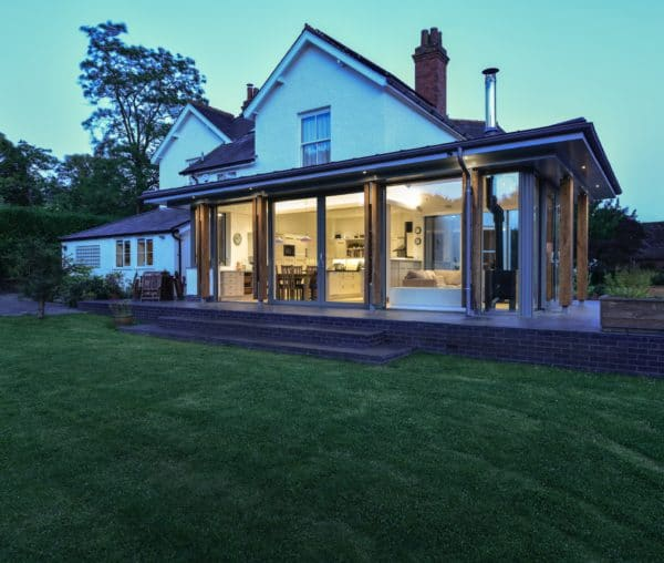 Exterior of home extension at twilight. The warm lighting inside the glazed extension brings focus to it, with the family dining room table inside, the original, white 1930s house rises behind. Communion Architects, Hereford.