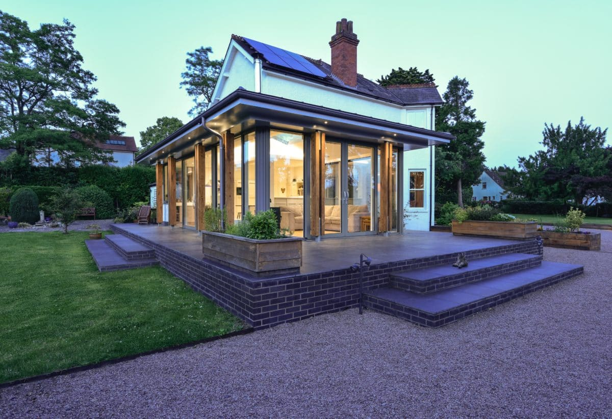 Corner image of house extension. The image highlights the fact the extension is simply walls of glass around all three sides. The dusk sky and warm interior lighting brings attention to the timber pillars which support the flat zinc roof which covers the glazed cube. Communion Architects, Hereford.