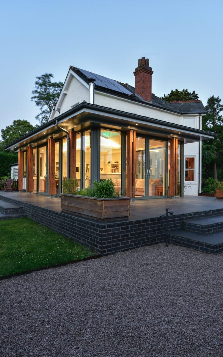 Portrait image of the extension, showing the corner of the extension and the two walls of glass in view. The twilight sky contrasts with the warm interior glow coming from the inside. Communion Architects, Hereford.