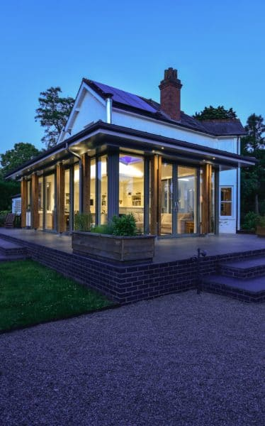 Indigo sky and warm bright lighting. A glazed and aluminium extension with a zinc roof. The extension is not dissimilar to a glazed cube as it sits snugly with the 1930s house behind. Communion Architects, Hereford.