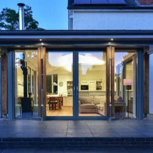 Home extension by dusk. Facing one of the three fully glazed walls to the extension the warm light inside highlight the welcoming living area inside. Inside one can see the grey corner sofa with a lot fire in the opposite corner and behind these is the family dining room table in this open plan extension. Communion Architects, Hereford.