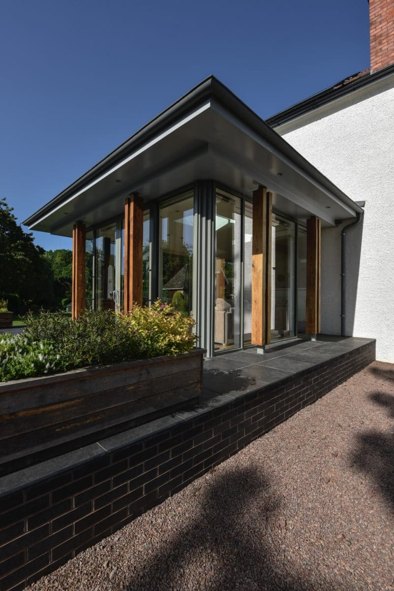 Angled close-up of a home extension by communion architects. A single storey extension with a zinc roof and full height glazing.