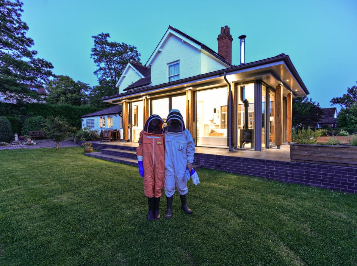 Our clients, standing in their bee keeping gear in from of their glazed extension at dusk. Proud owners of their light-filled living area which has transformed their space and transformed their lives. Communion Architects, Hereford.
