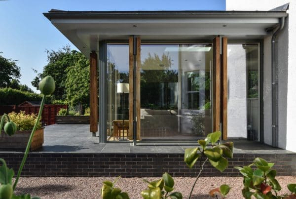Side view of home extension by communion architects, Herefordshire. Image shows flat, over hanging roof projecting full height glazing, framed with aluminium and timber columns on a raised patio.