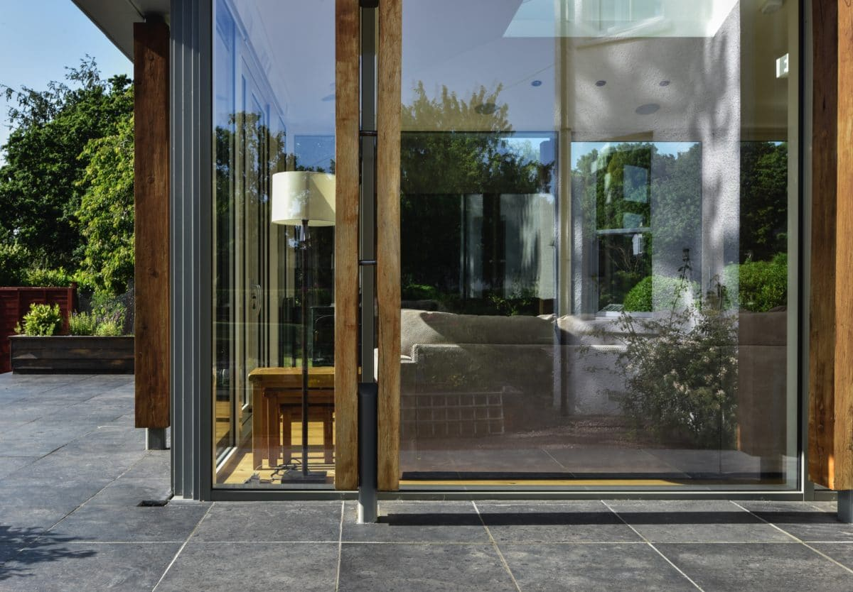 Home Extension. The lower third of the frame is a stone patio, the upper two thirds show a portion of the glazed extension, inside a seating area can be seen. Communion Architects Herefordshire.
