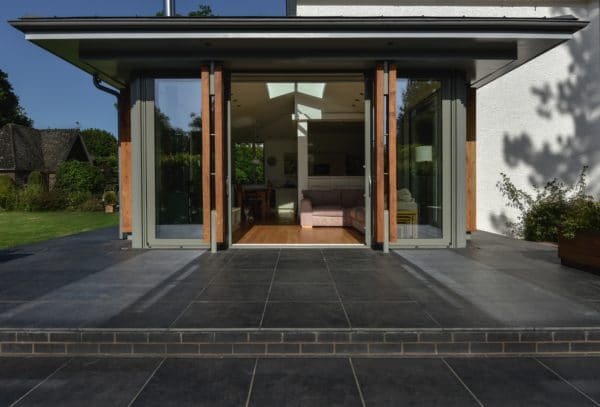 Glazed Home extension, image shows the bi-folding doors opening out on to a slate patio. Communion Architects. Hereford.