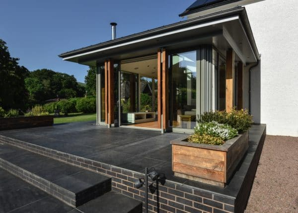Home Extension, image shows steps up to a slate patio, which leads to the glazed living area. Communion Architects, Herefordshire.