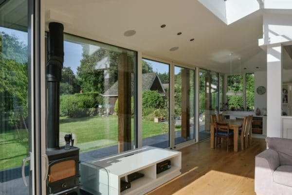 Interior of home extension. Interior shows three walls of glazing with a roof opening to create a light-filled living area. Inside is a fire place and coffee table, from this table will rise a tv. Communion architects, Herefordshire.
