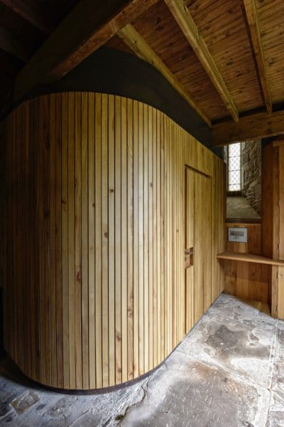A cube-like structure made from timber with a door, an accessible toilet (unseen), st Michael and All Angels, church re-ordering