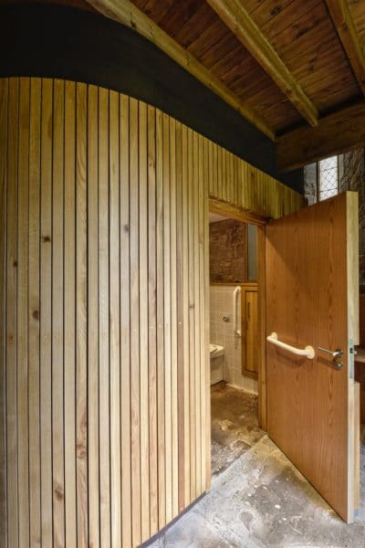 A timber cube-like structure, door open to reveal an accessible toilet, St Michael and All Angels, church re-ordering.
