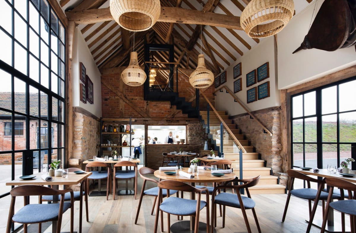 Interior of Pensons Restaurant on the Herefordshire/Worcestershire border. This was a derelict 16th century barn which has been transformed into a light-filed Michelin starred restaurant by Communion Architects. Two large steel-framed windows are opposite each other, between them is a timber floor with several wooden tables and chairs. Down the the length of the former barn is the open kitchen with chefs busy cooking. At the end on the right hand side is a floating staircase leading to a first floor private dining room. The walls have exposed stone and the rafters are painted white with exposed timber beams. From these hang four handwoven wicker lampshades. Communion Architects, Barn Conversion, Herefordshire.