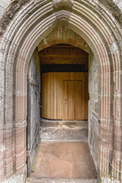 doorway too interior of st Micheal's and all angels. Stone external archway framing a timber cube-like structure inside. Church Re-ordering.