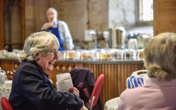Two women enjoying the 'Take a Pew' cafe at St Michael's and All Angels. The church re-ordering allows the church to host such events.