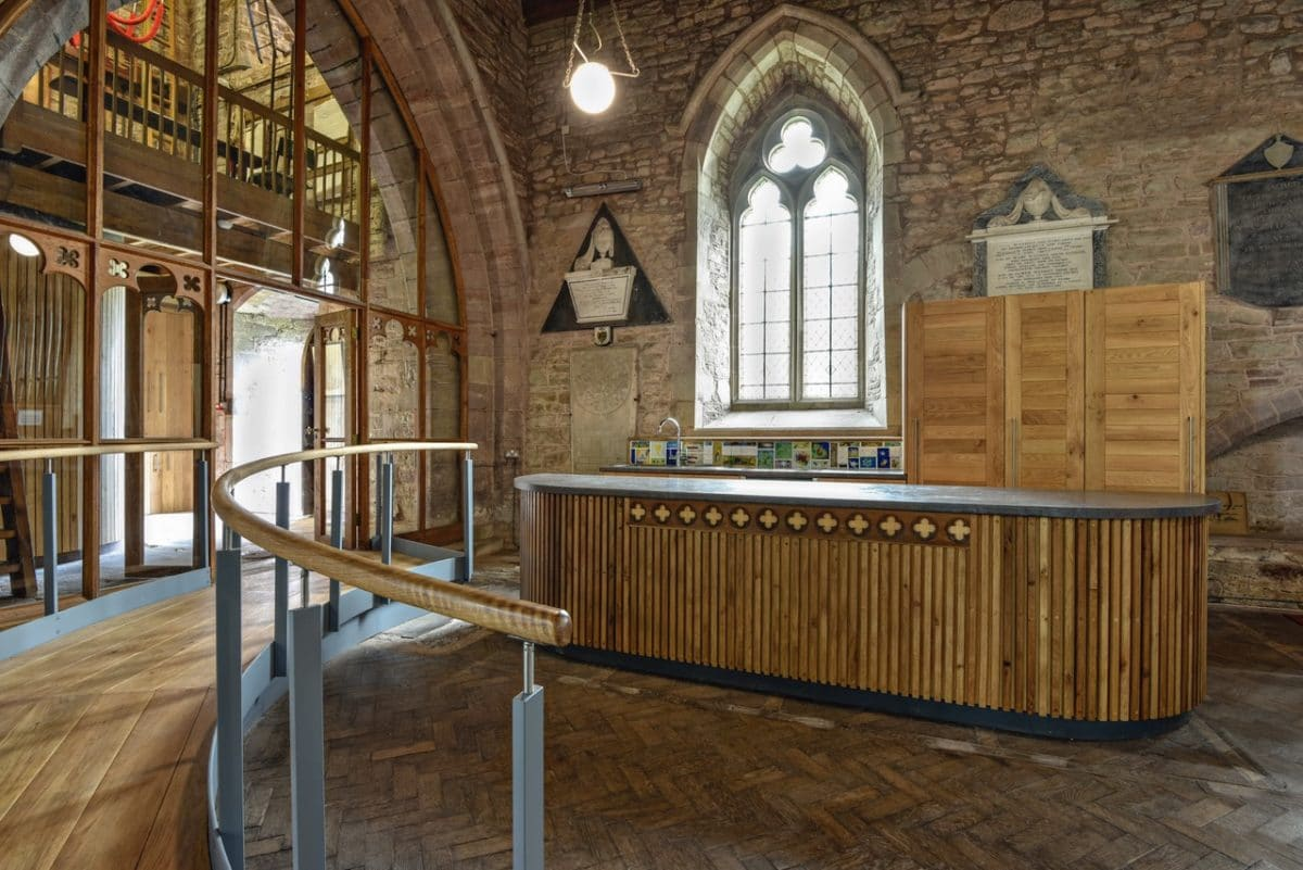 Interior of St Micheal's and All Angels, a church re-ordering. image featured a curving ramp for accessibility and a timber kitchen area with island and cupboards.