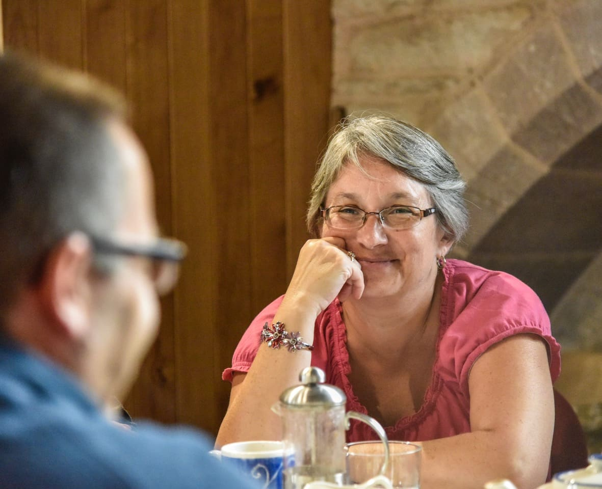 A person engaged in conversation at the 'Take a Pew' cafe at St Michael's and All Angels. The church re-ordering allows the church to host such events.