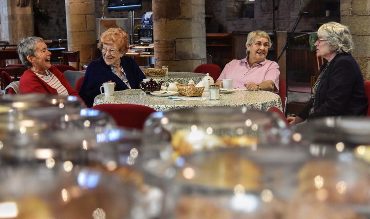 Four older ladies sit around a table in st Michaels and all angels at the 'Take a Pew' event, church re-ordering project.