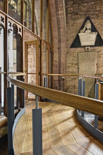 Close up of ramp and banisters. Wooden balustrade supported by metal columns, with wooden pathway. Interior St Michael and All Angels, church re-ordering.