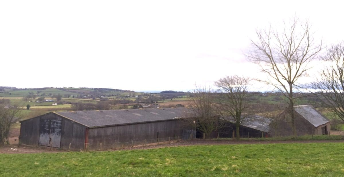 At the bottom of a green field is a long dark grey barn. Industrial style agricultural barn with potential for a barn conversion. The view behind shows the beautiful rolling hills of Herefordshire. transforming space, Communion Architects, Herefordshire.