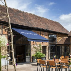 Exterior of Pensons restaurant, in the foreground is seating in the courtyard area, in the background is the restaurant, a 16th century barn with stone foundations, timber supports, red brick and a clay tiled roof.