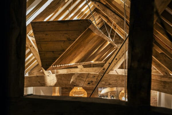 Pensons Restaurant ceiling. Showing a long timber manger running the length of the ceiling, reimagined as a lighting rig. Barn conversion project
