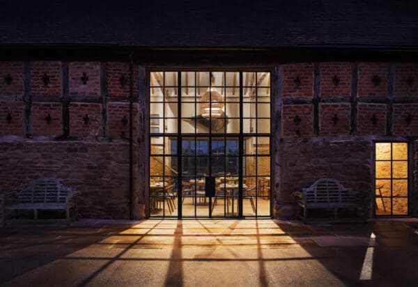 Exterior of Pensons Restaurant at dusk. Image shows the stone, brick and timber exterior with full height, steel-framed window lit from inside, in the centre of the image. A barn conversion project.