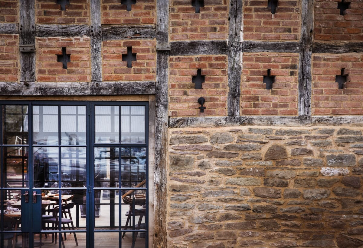 Pensons restaurant. Close-up of the exterior wall, bottom right is stone, bottom left is a new steel-framed window, above both is a timber frame with red brick inserts. barn conversion